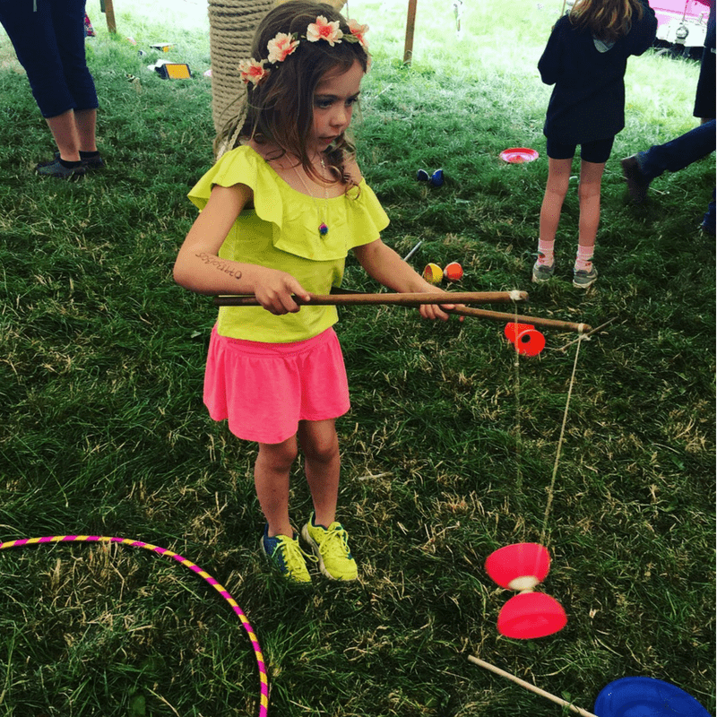 girl playing with a yoya wearing a flower headband at a family friendly music festival