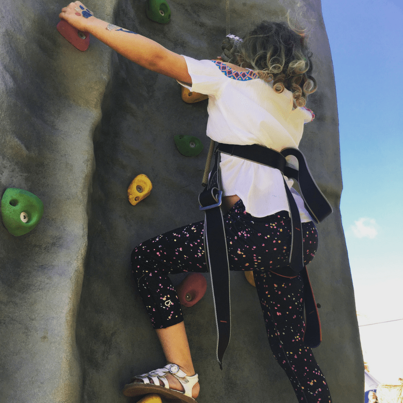 girl climbing a rock wall in the kids field at glastonbury festival