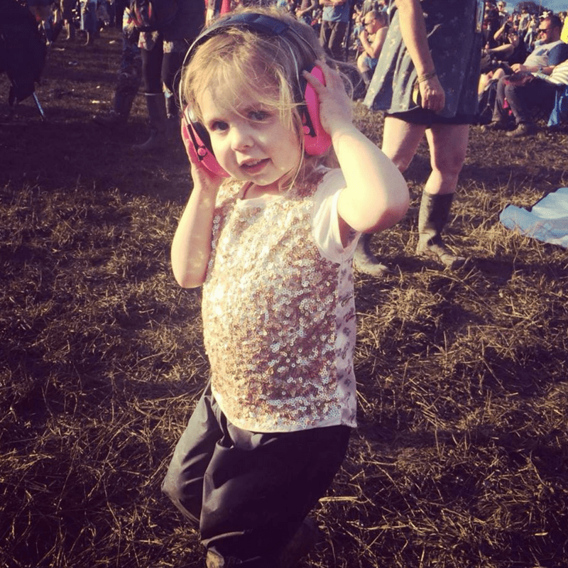 toddler wearing ear phones in a sparkly top at glastonbury festival