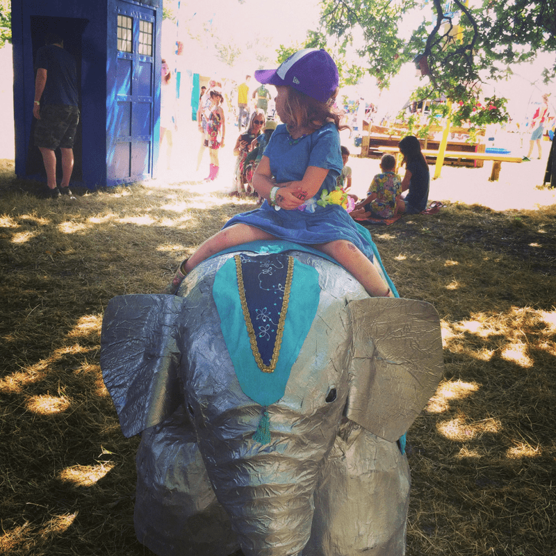 girl sitting on top of a paper ache elephant infant of the tardis