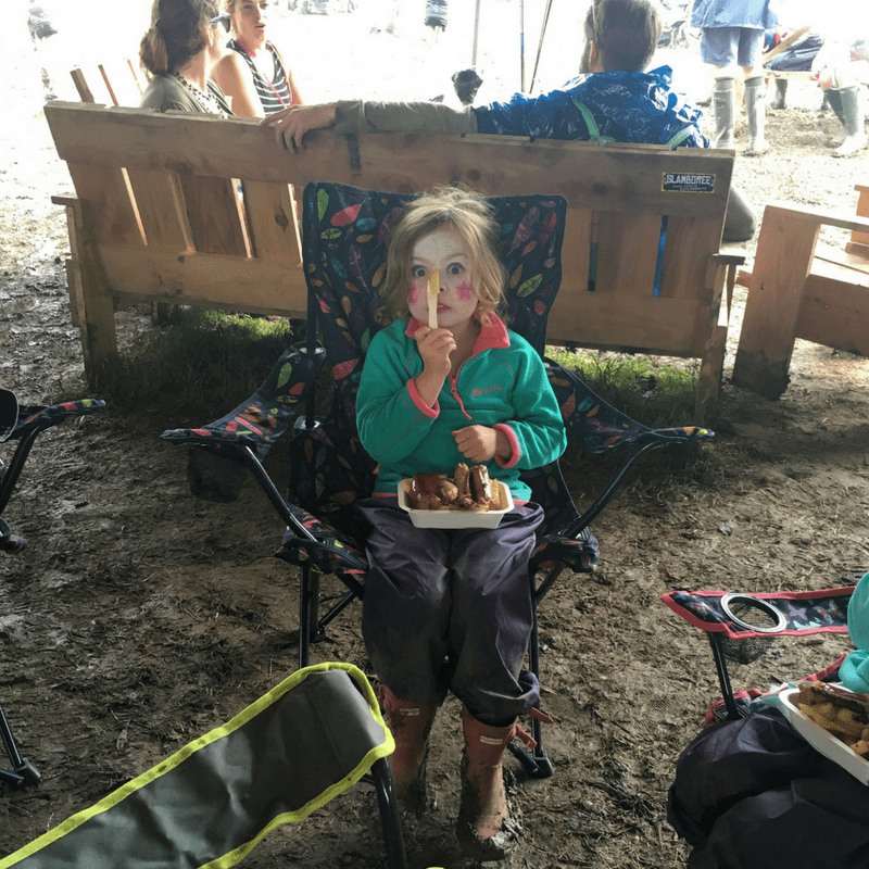 girl with clown faceprint eating a bowl of chips at a very muddy glastonbury festival
