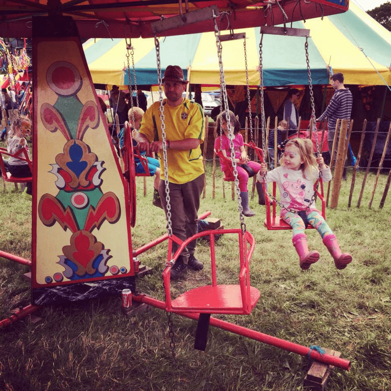 girl on traditional swings ride in the kids field at glastonbury