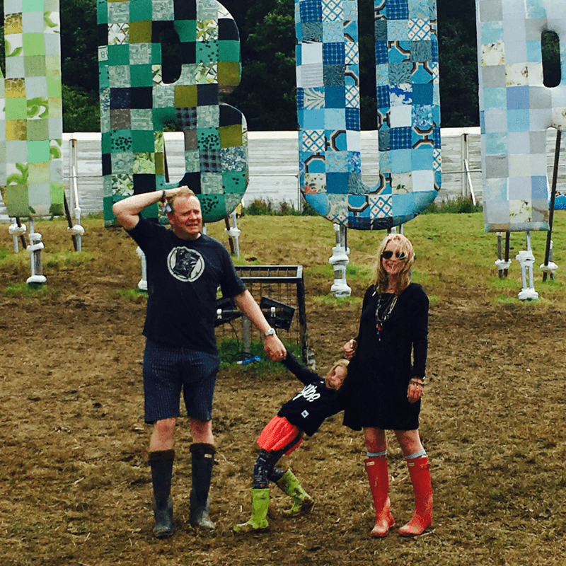 family of three standing outside the glastonbury sign all in wellies