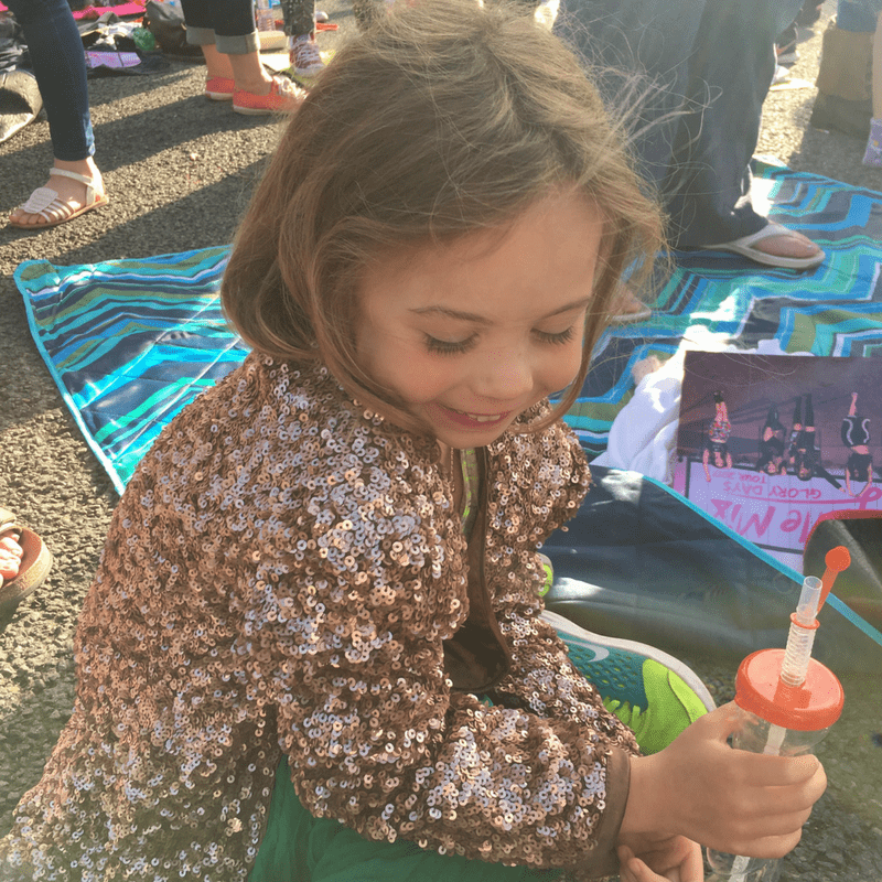 girl is sparkly jacket watching live music at a family friendly festival