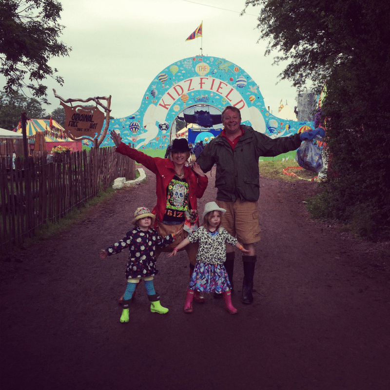family of four posing outside the kids field at glastonbury on a rainy day