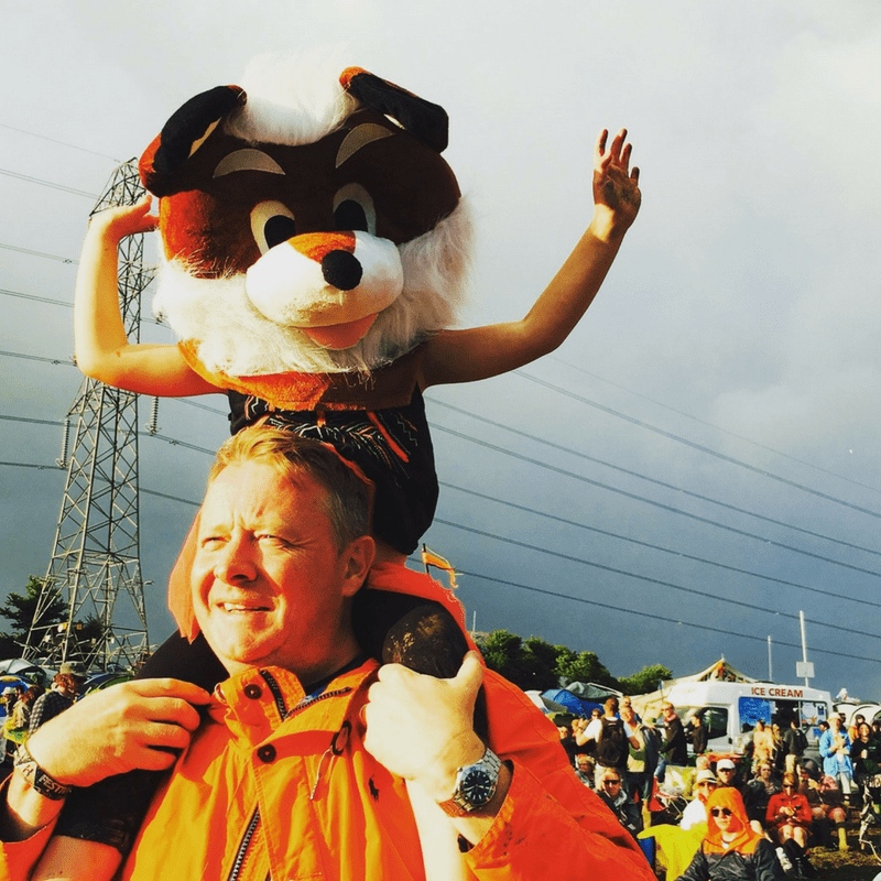 girl on her dads shoulders wearing a huge fox head mask waving her hands in the air at glastonbury