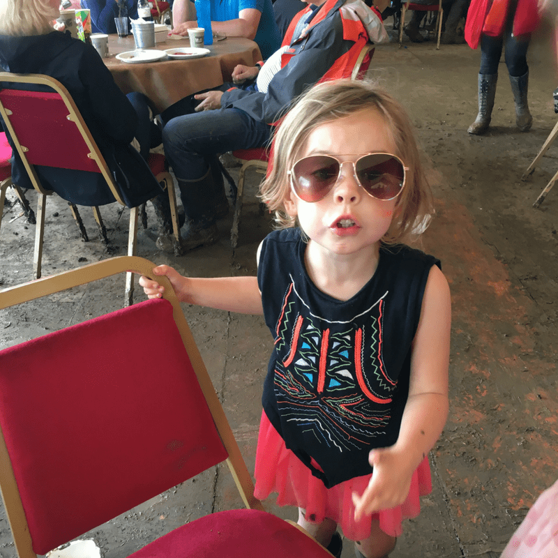 young girl in huge aviator sunglasses in the muddy hospitality area at glastonbury