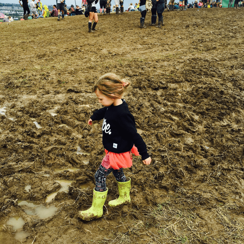 girl playing in maud wearing a tutu and wellies at a family friendly festival