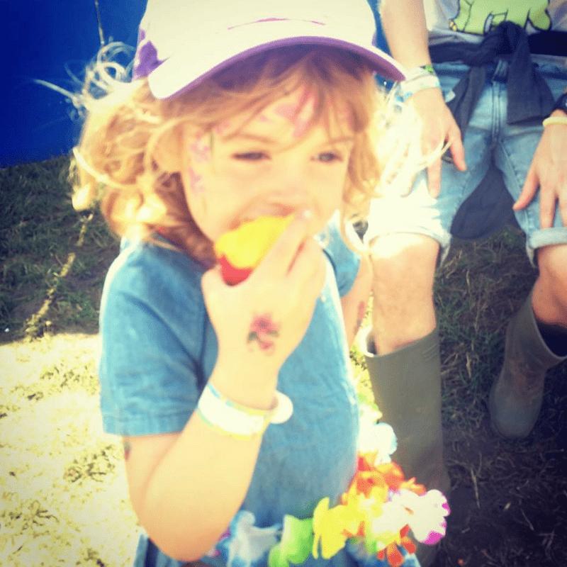 girl eating each peach in the sunshine at glastonbury