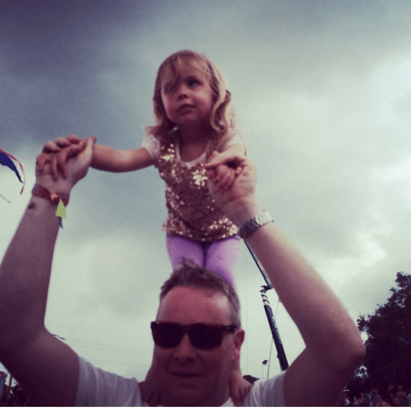 young girl standing on her dads shoulders at glastonbury festival