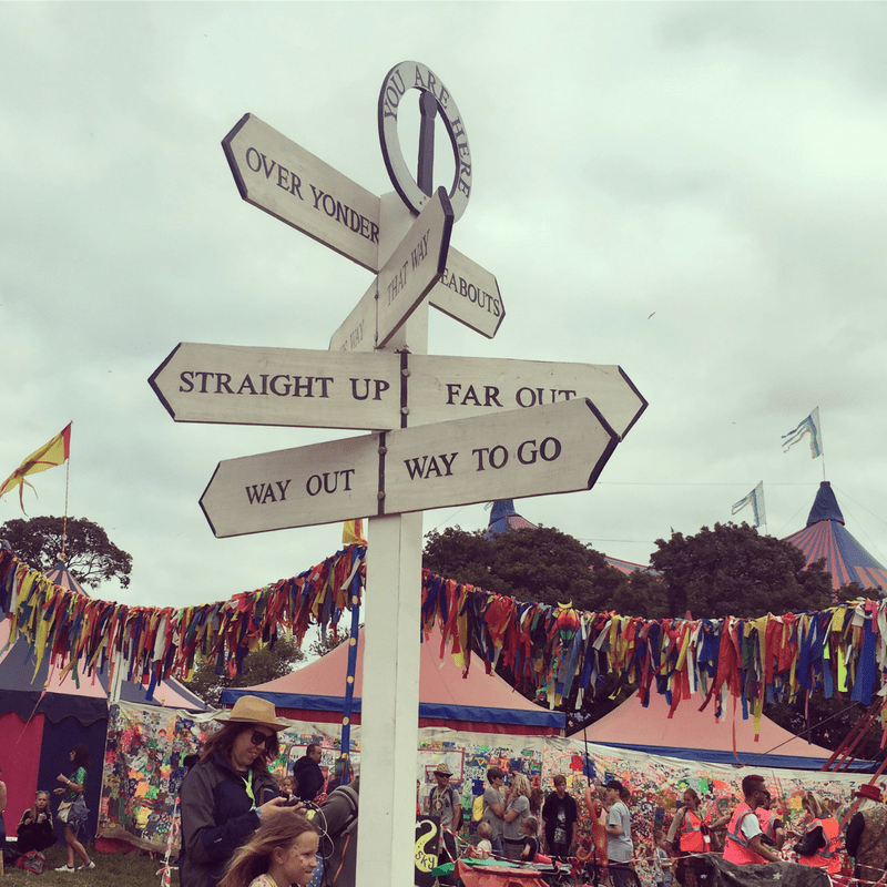 fun road sign at glastonbury festival against a foggy grey sky