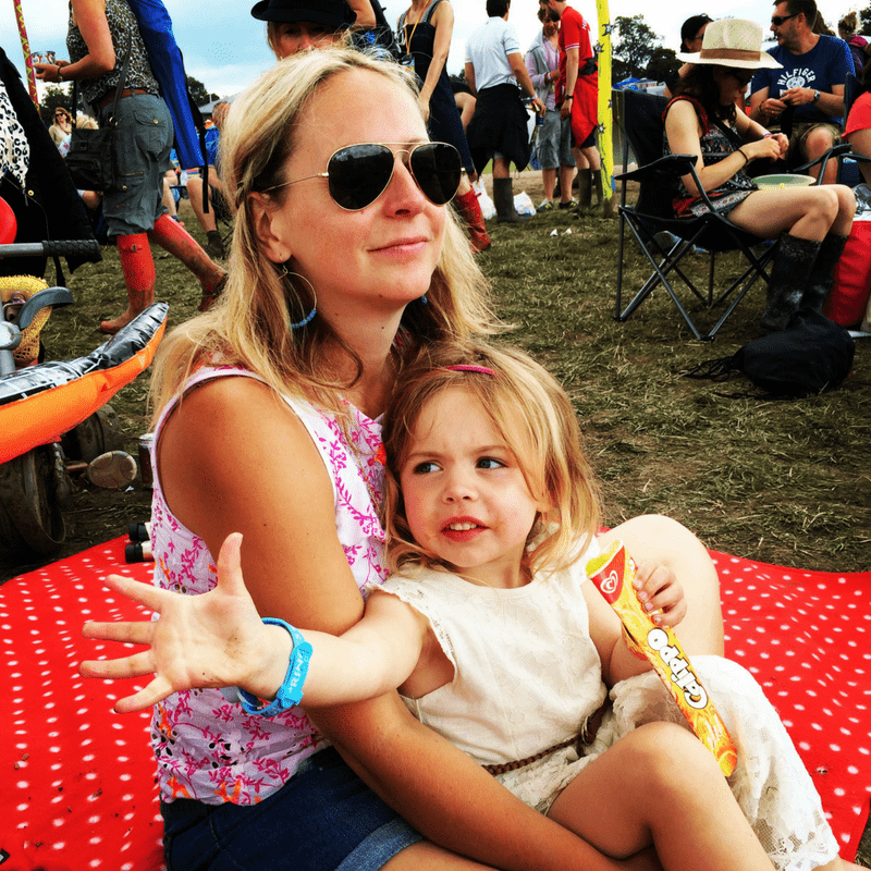 blonde mother and daughter in sunglasses watching live music at a family friendly festival