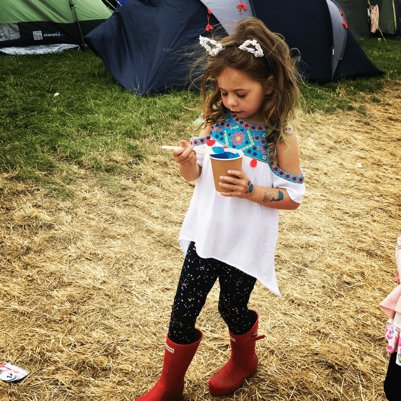 girl in red wellies eating ice-cream wearing cat ears at music festival