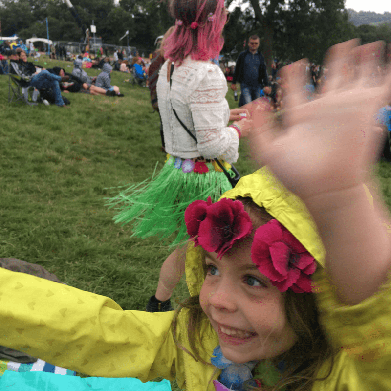 young girl wearing flower headband and yellow raincoat dancing in a field