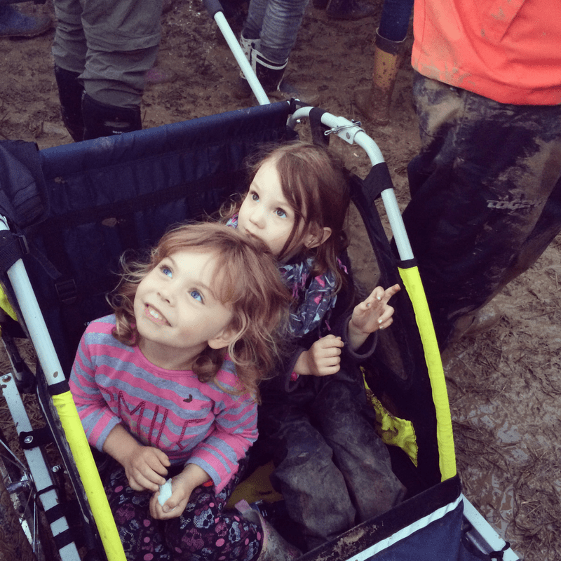 two smiling girls sitting in a trailer at a muddy glastonbury festival