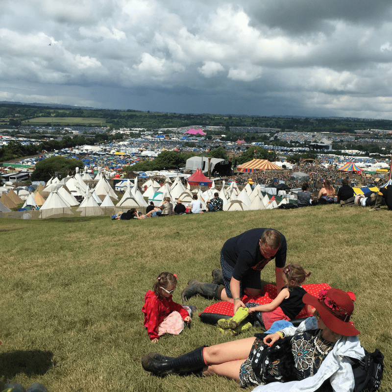 view of teepee field at glastonbury festival on top of a grassy hill