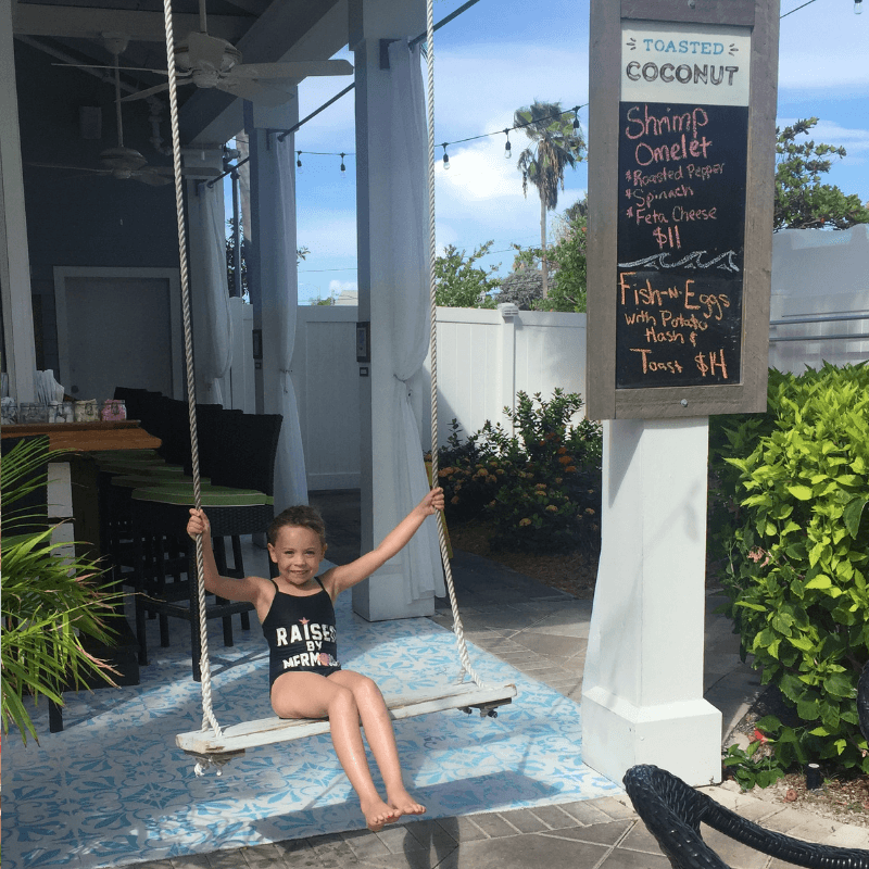 girl on swing at the toasted coconut restaurant in key west