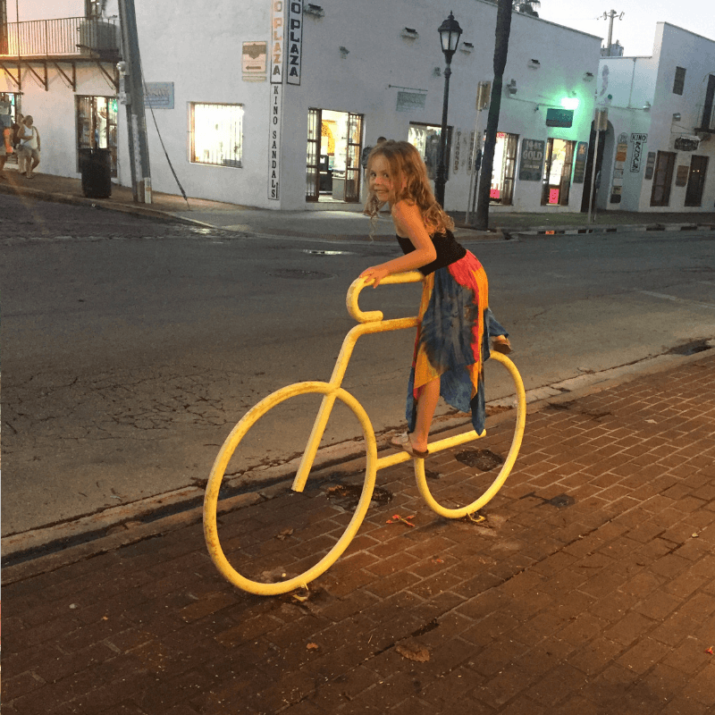 young girl climbing on bike rack in key west