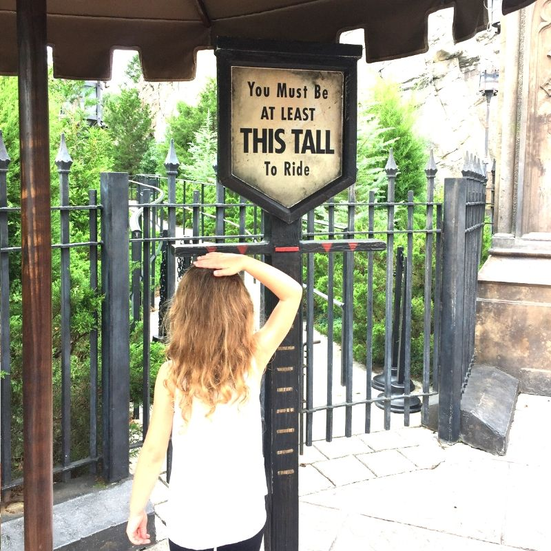 girl checking her height at the wizarding world of harry potter at universal studios
