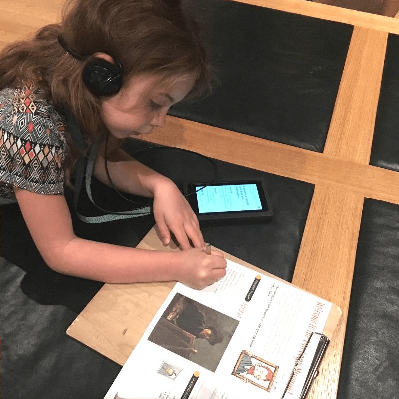 tween girl wearing headphones completing a scavenger hunt at the van gogh museum, amsterdam