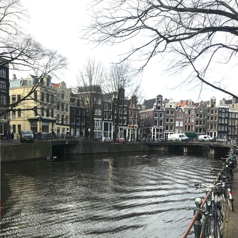 narrow houses along the river in amsterdam
