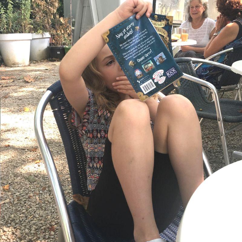 tween girl reading book in vondelpark, amsterdam