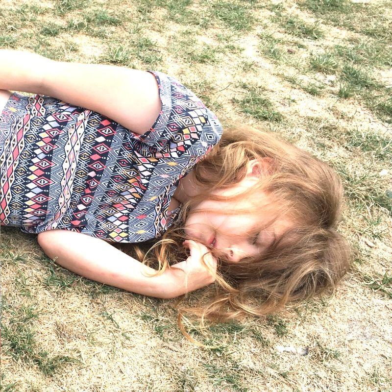 tween girl asleep on grass in vondelpark, amsterdam