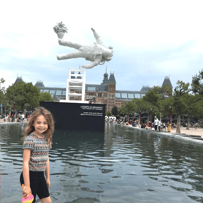 tween girl outside klibanskys self portrait of a dreamer statue in amsterdam
