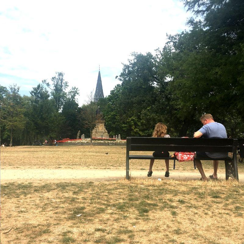 fater sat on a bench with tween daughter in vondelpark, amsterdam