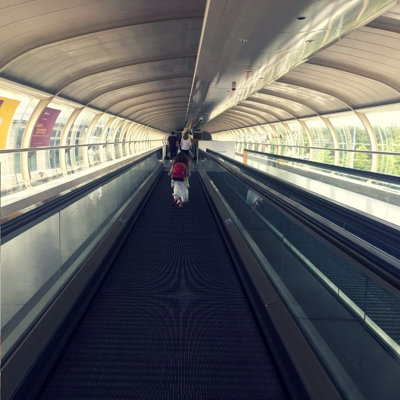 girl running through connection tunnel at an airport. She is carrying a back pack on her back