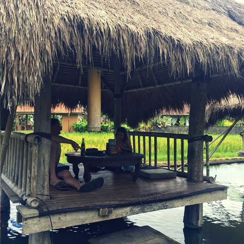 girl and her father sat at a restaurant on stilts over a lake