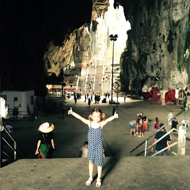 girl giving thumbs up after reaching the top of the batu caves