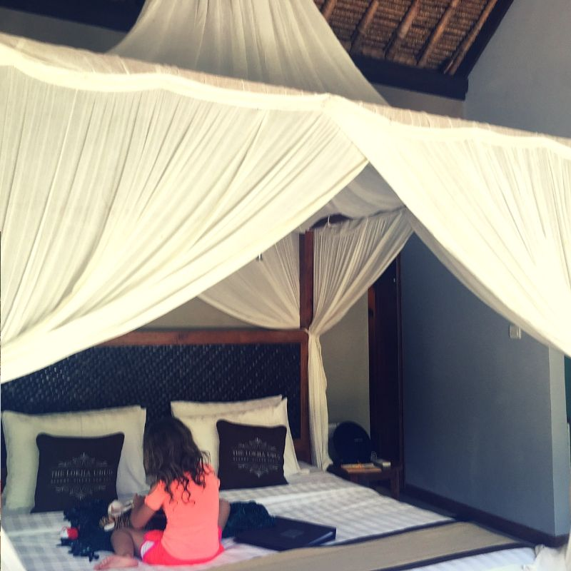 girl sat on huge four poster bed at the Lokha hotel in Ubud, bali
