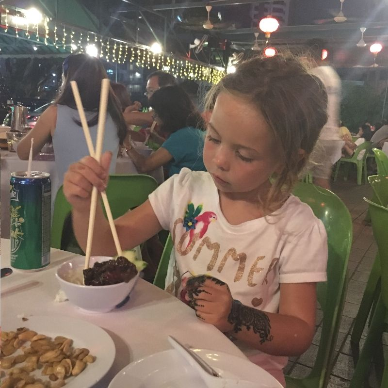 blonde girl eating her dinner with chopsticks in Kuala lumpur