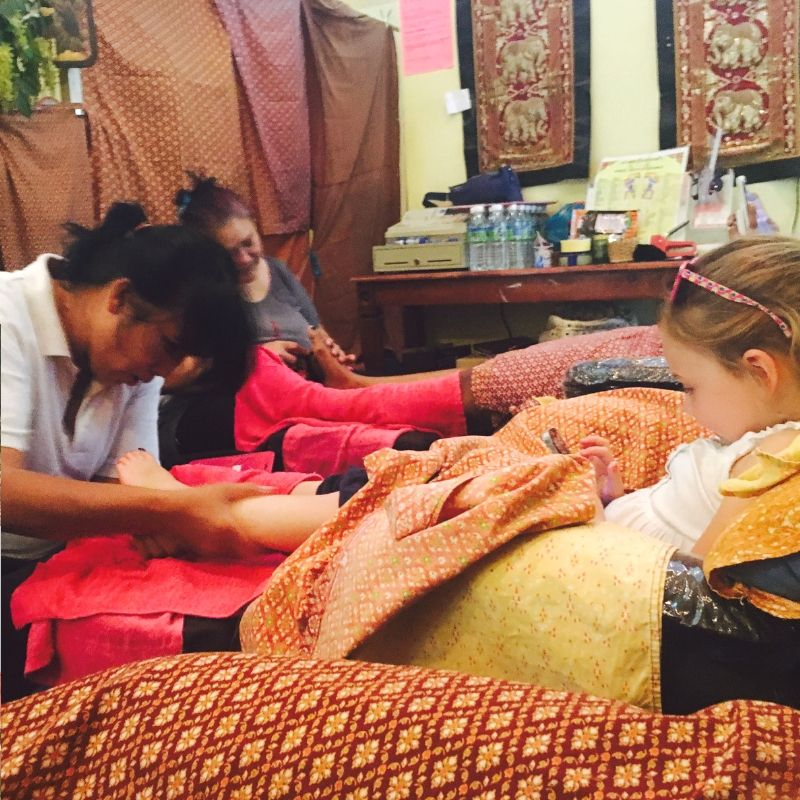 young girl getting a foot massage while playing on her phone in thailand