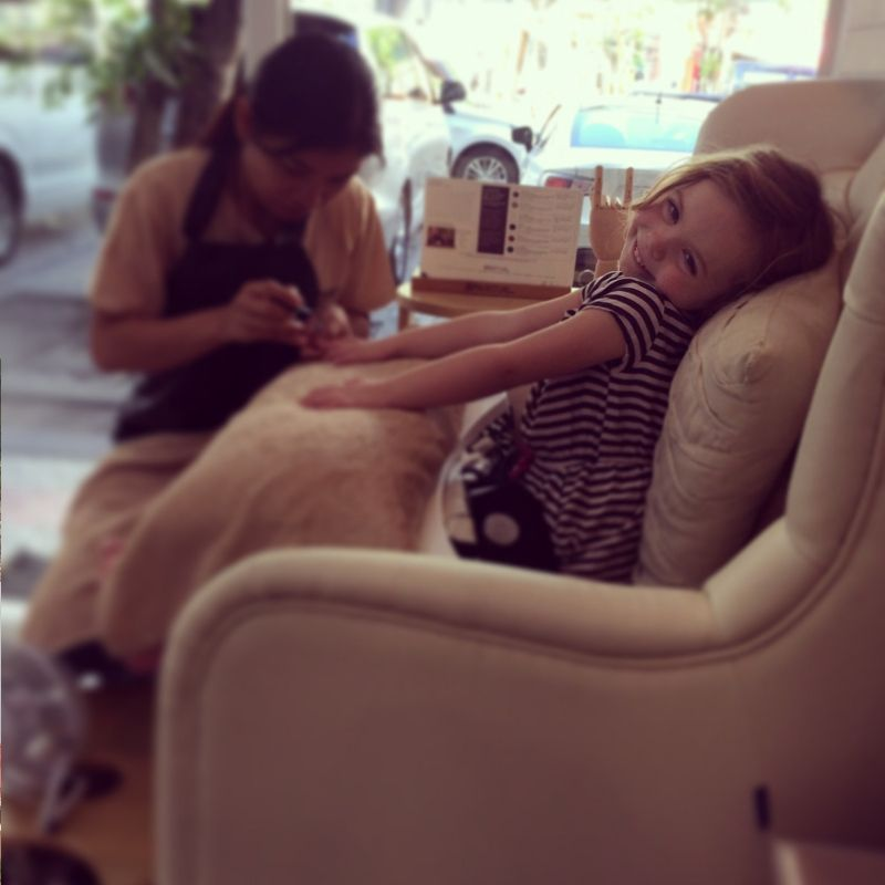 young blonde girl getting her nails painted with a big smile on her face