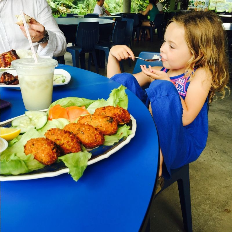 blonde girl in blue maxi dress eating street food at a hawker centre in singapore