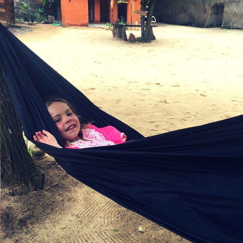girl in pink dress peeking out of black hammock in bali