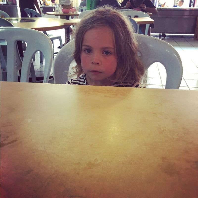 young blonde girl looking sad sat at a table in a food hall in kuala lumpur