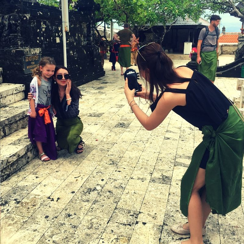 young girl being photographed by tourists in a temple in Thailand