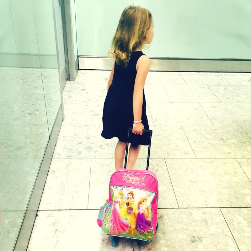 young girl in a blue dress pulling a small suitcase through an airport