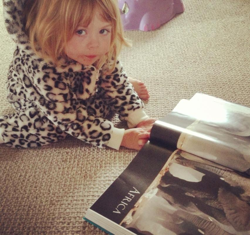 toddler girl in a furry onesie reading a book about africa