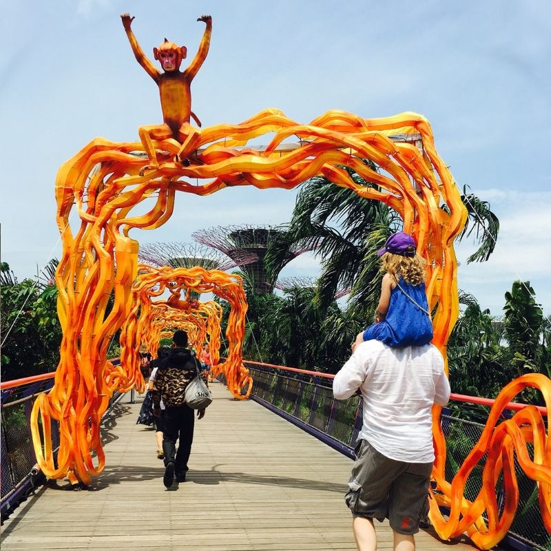 girl in cap on her fathers shoulder walking down a bridge with an orange monkey on top over looking the super trees in singapore
