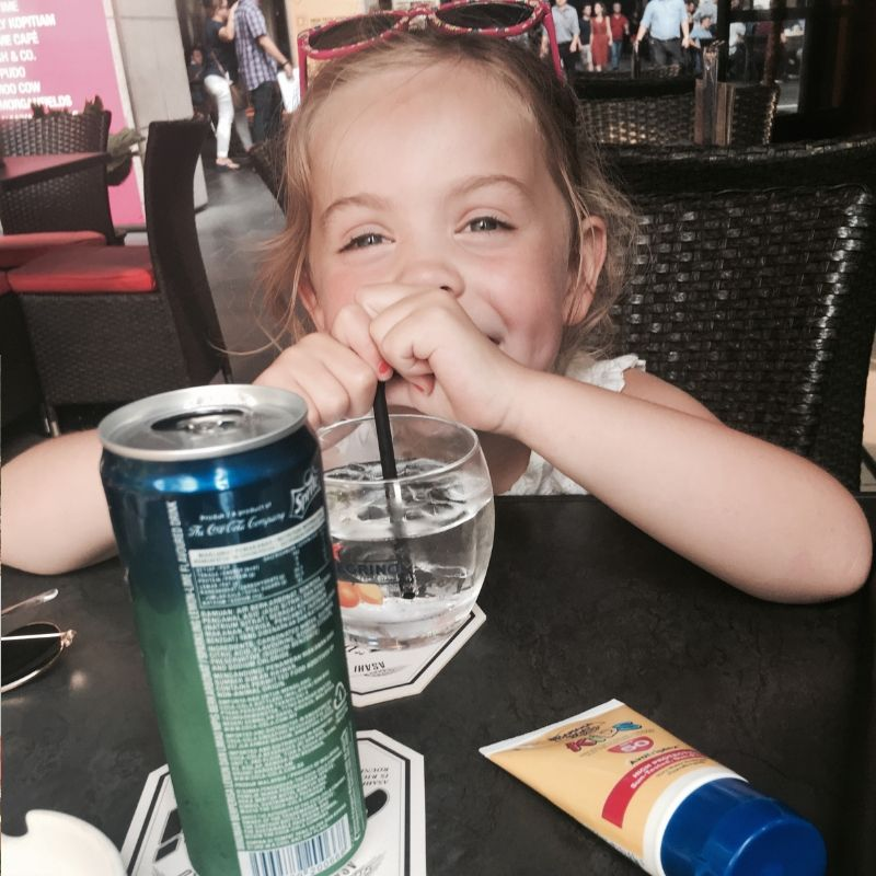smiling blonde 6 year old, sitting in a cafe drinking a lemonade