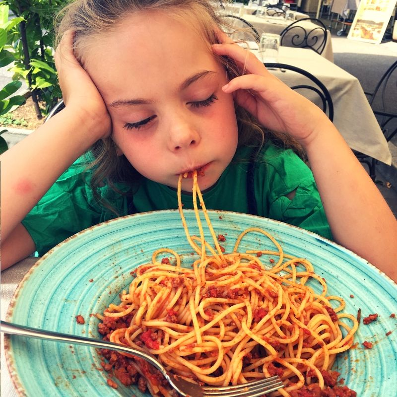young girl falling asleep whilst eating a bowl of spaghatti bolognaise