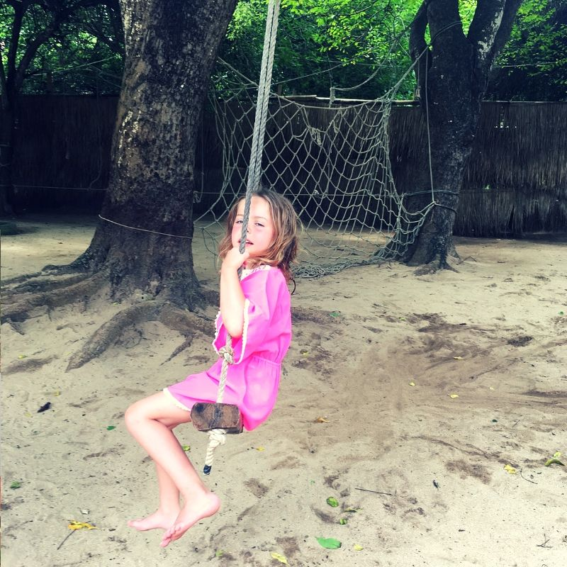 girl on a wooden swing in asia