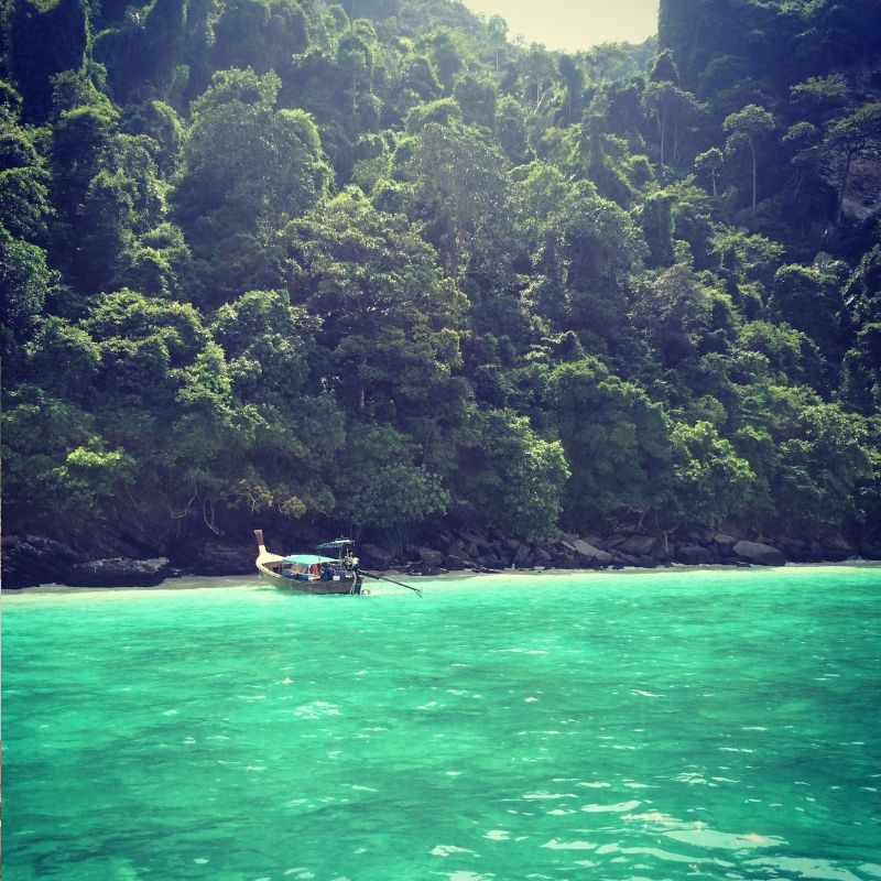 thai fishing boat moored next to a deserted island near Koh Phi Phi in Thailand