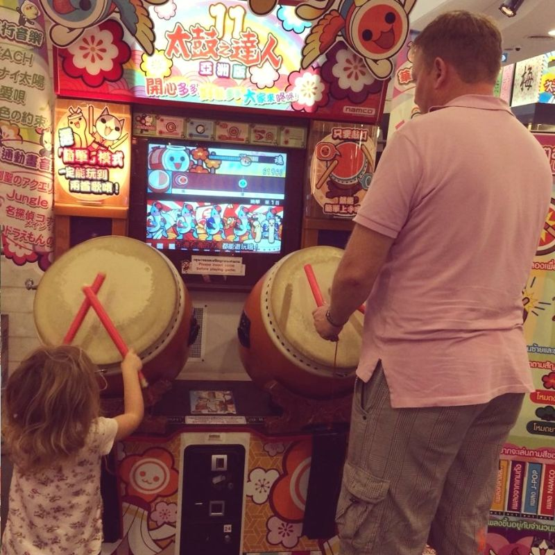 young girl and father playing drumming arcade game in bangkok