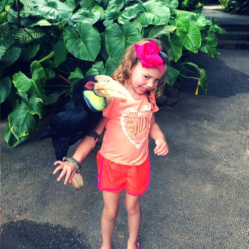young blonde girl in orange t shirt with a huge toucan on her arm