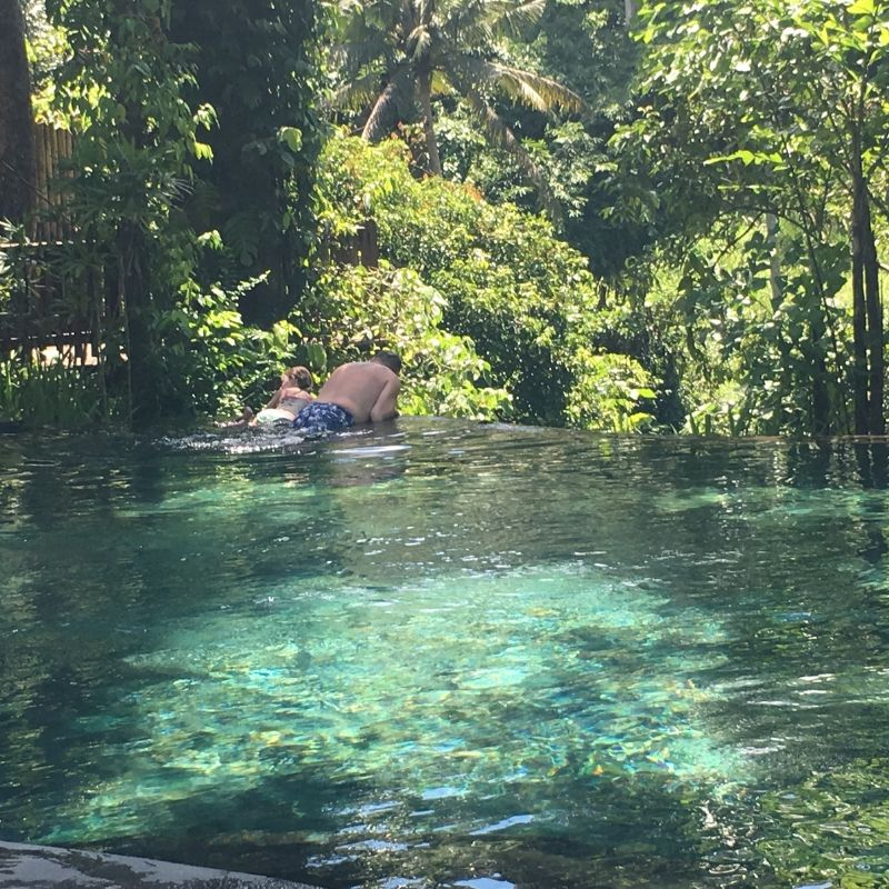girl and father swimming in an infinity pool overlooking the jungle in ubud, bali